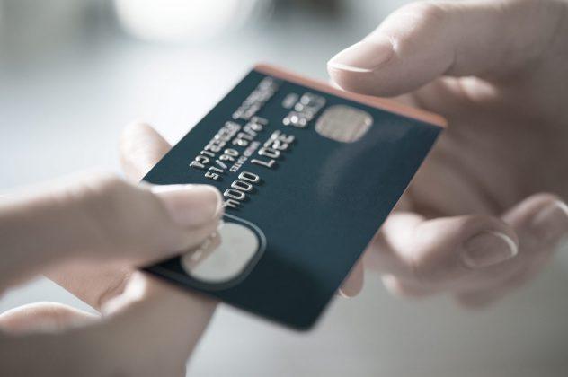 Kreditkarte wird zum Kauf übergeben